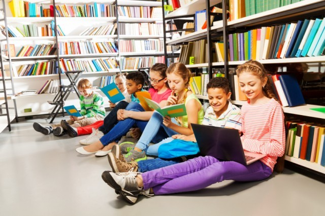 Children reading and learning from a laptop in a library