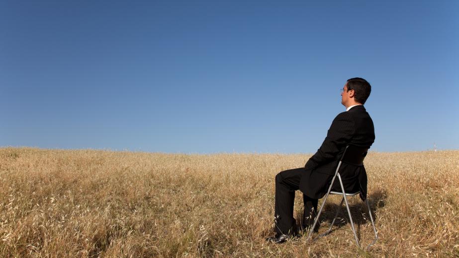 Man sitting in a cornfield in a suit