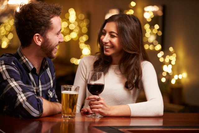 Man and woman enjoying beer and wine at restaurant.