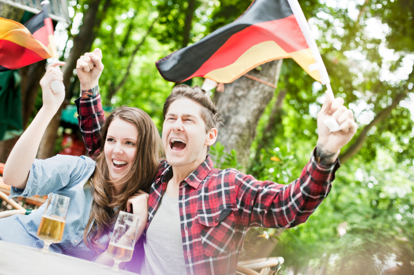 Couple celebrating Germany's sports vicotry at a country pub., sporting event