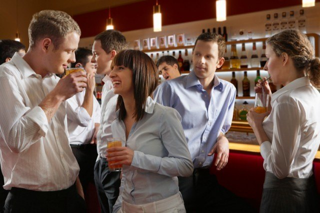 Male and female employees talking at a bar