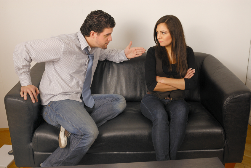 Man and woman talking on a couch