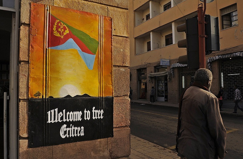 A man waits to cross the road beside a patriotic poster in Asmara, Eritrea