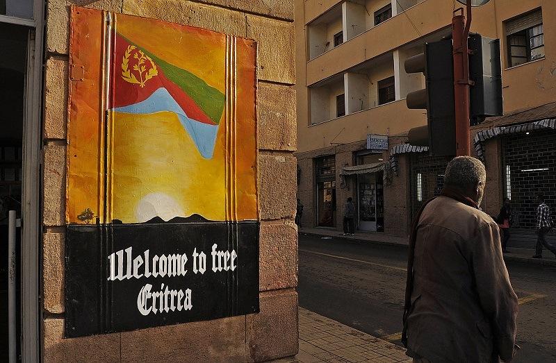 A man waits to cross the road beside a patriotic poster in Asmara, Eritrea