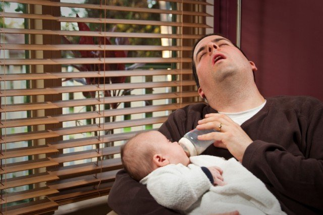 man falling asleep while feeding a baby