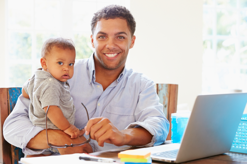 dad holding baby while working from home