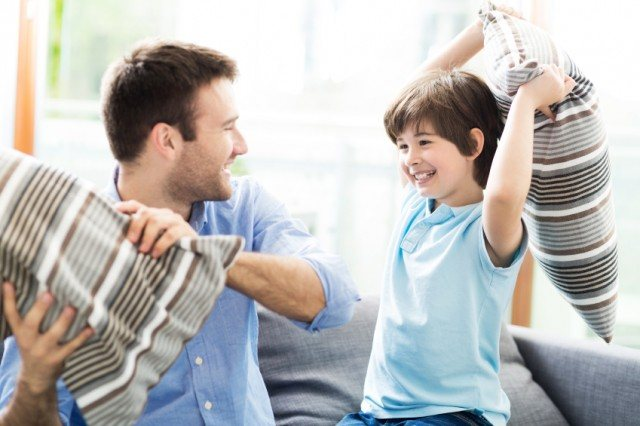 Father and son having a pillow fight