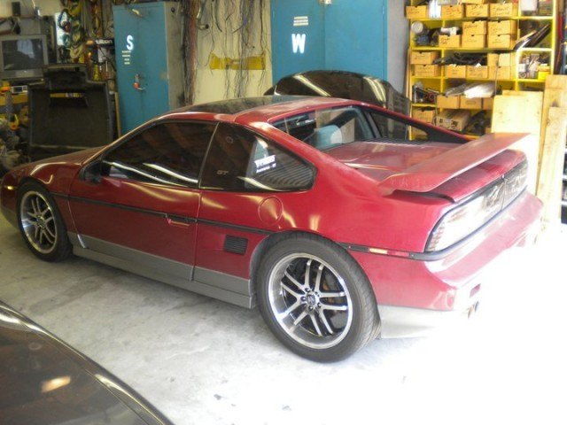 A red Pontiac Fiero sits parked inside a garage