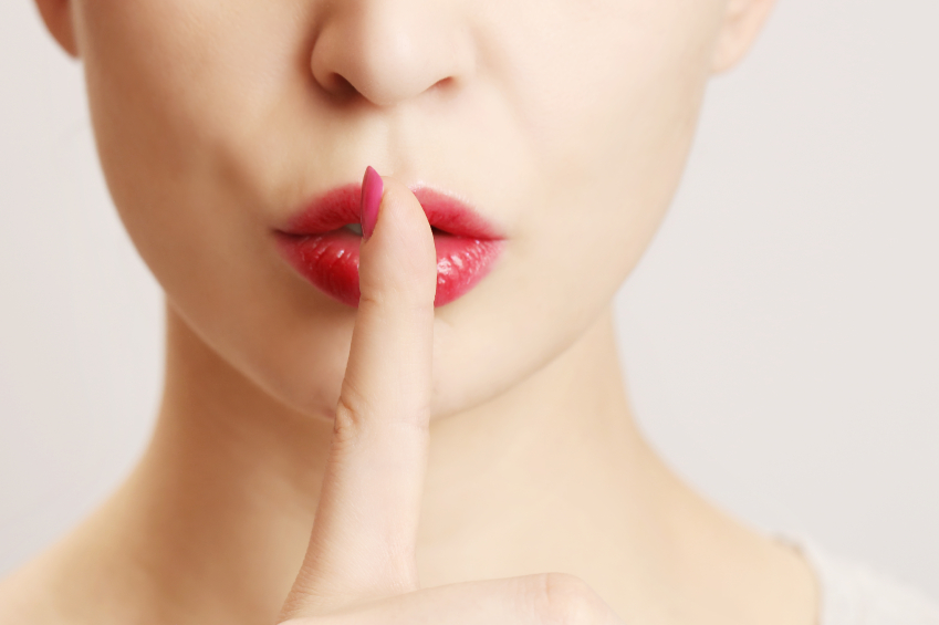 woman holding finger to lips in shh