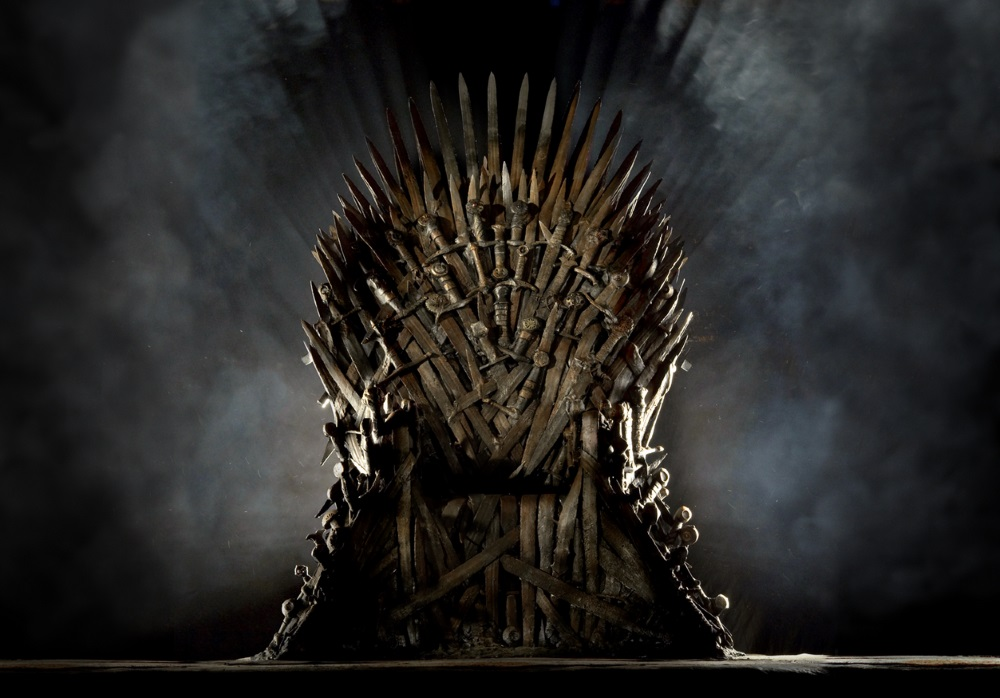The Iron Throne, empty and sitting up against a grey, smokey background