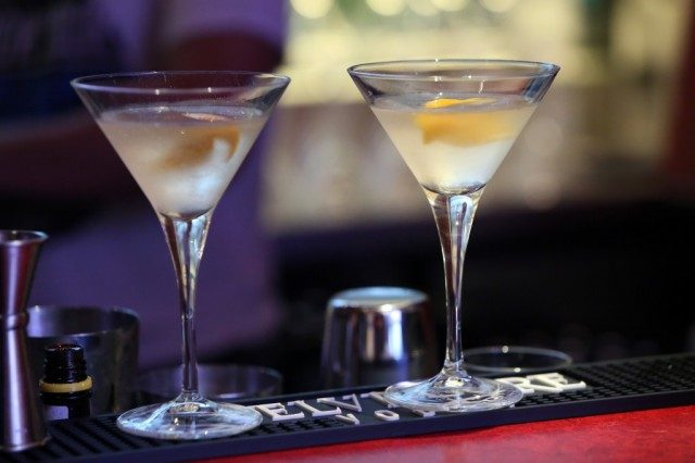 Two martini glasses with garnish.