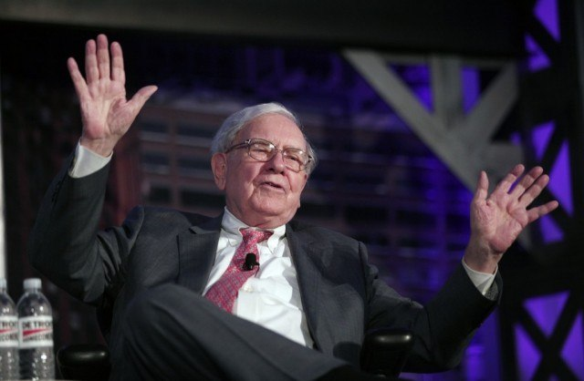 Warren Buffet speaks while holding his hands up.
