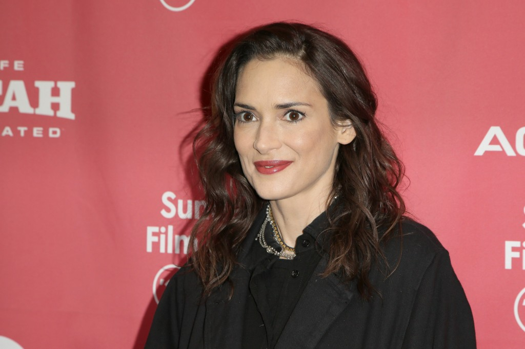Winona Ryder is smiling on the red carpet in a black outfit.