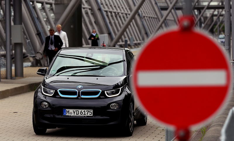 A black BMW i3 drives down the street