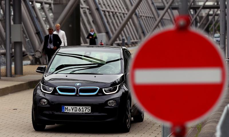 A black BMW i3 drives down the street