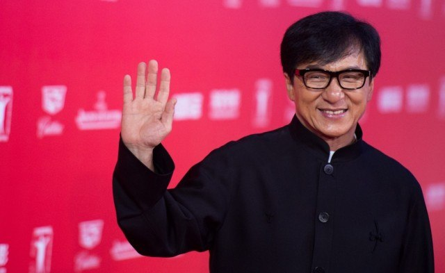 Jackie Chan holds up his hand in a wave while walking the red carpet