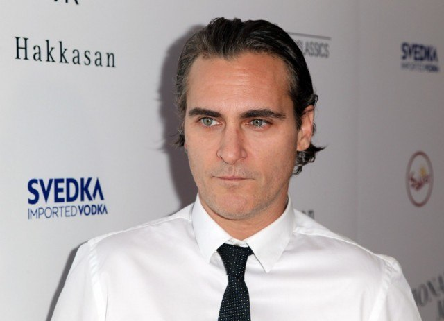 Joaquin Phoenix wearing a white shirt and black tie on a red carpet.