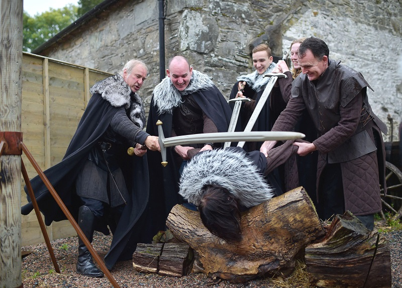 a group of men holding swords over someone