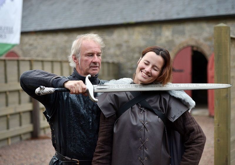 A man holding a sword by a woman