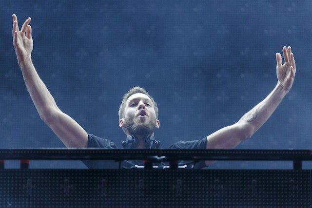 Calvin Harris has his arms up behind the DJ booth.