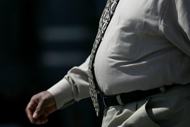 an overweight man walking to work