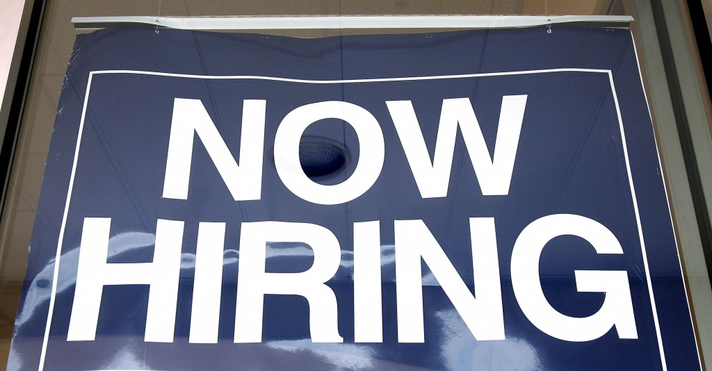 "A ""now hiring"" sign seen in a window"
