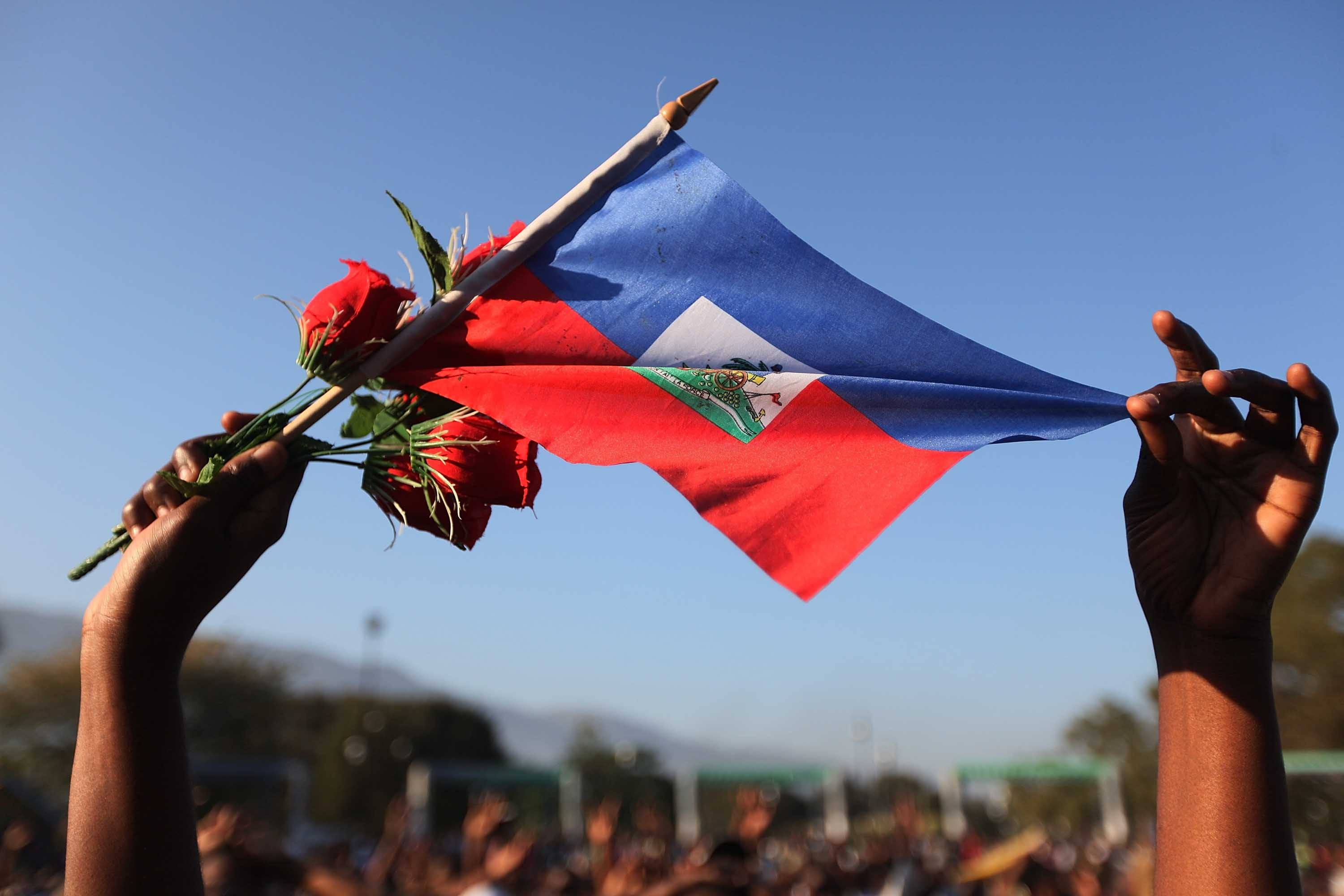 A woman holds a Haitian flag and roses