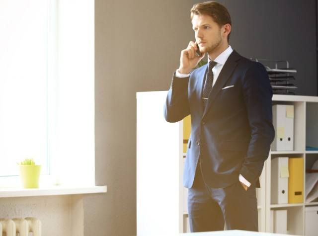 A man in a suit talking on the phone
