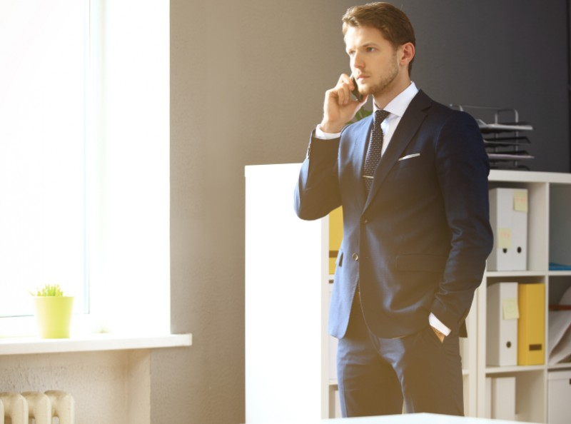 Handsome businessman in suit speaking on the phone in office, suit, style