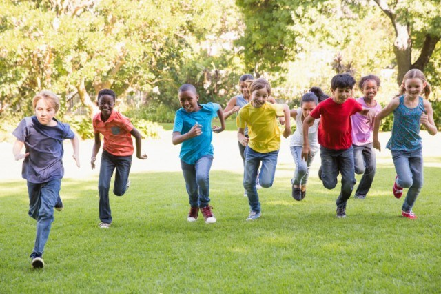 group of kids running through the park