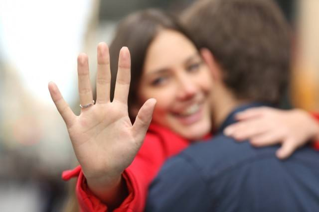 Happy woman showing engagement ring after proposal