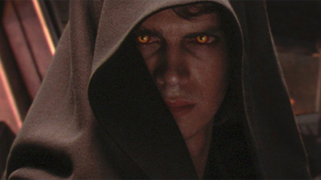 Hayden Christensen as Anakin Skywalker with glowing yellow eyes looking serious under a brown hooded cloak in Star Wars: Episode III -- Revenge of the Sith