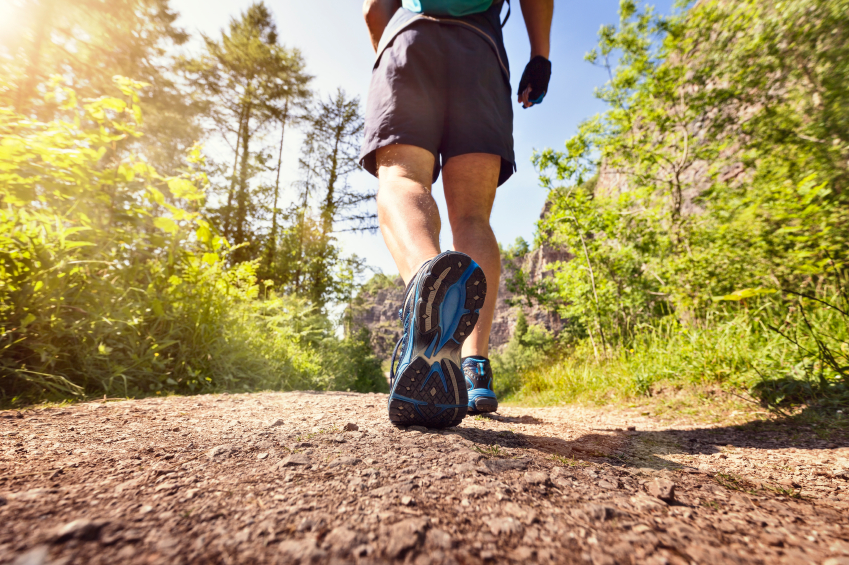 Man jogging or waking outdoors on a footpath or trail concept for healthy lifestyle, sport exercising, running and fitness