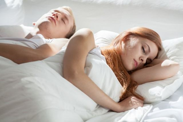 Husband and wife asleep in a bed