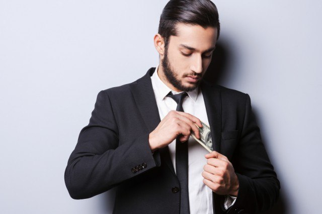 Man pulling money out of jacket pocket