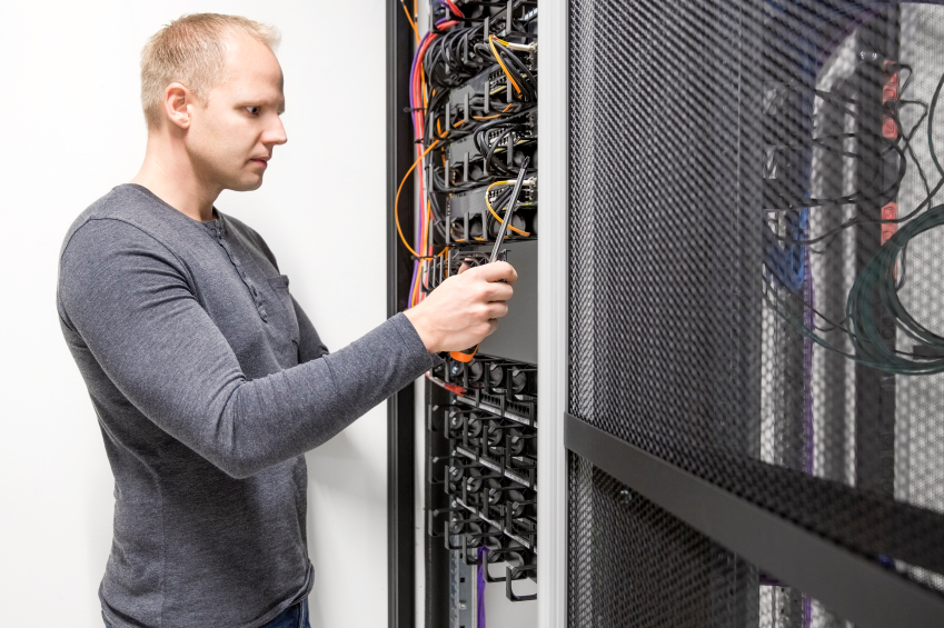 IT engineer or technician builds communication network rack for ethernet and fibre switches in datacenter