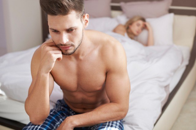Man looking forlorn on the edge of his bed