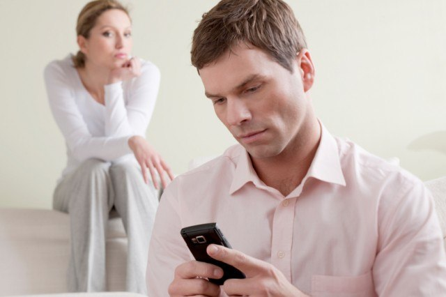 Man on phone while woman is suspicious