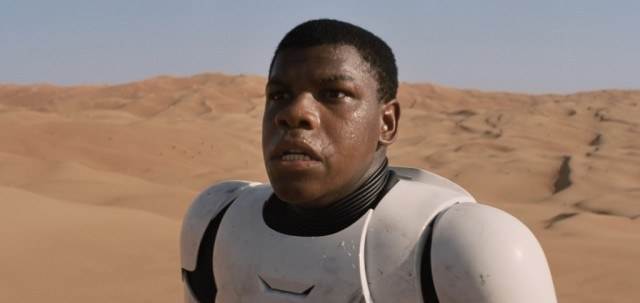 John Boyega stands in a desert while sweating and panting.