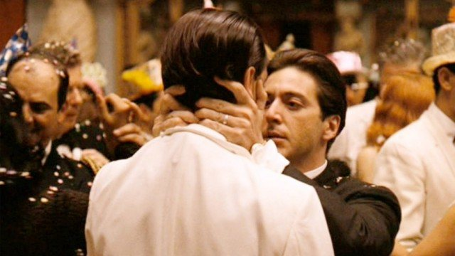 Michael Corleone holds Fredo's face at a party in The Godfather.