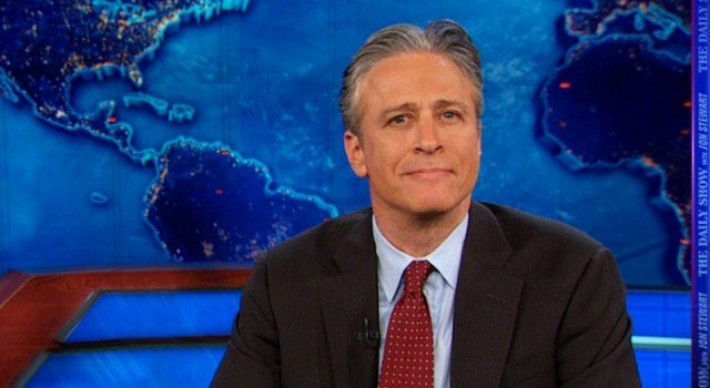 Jon Stewart sitting at a desk on his show.