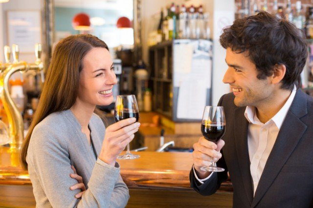 Two friends enjoy glasses of red wine.