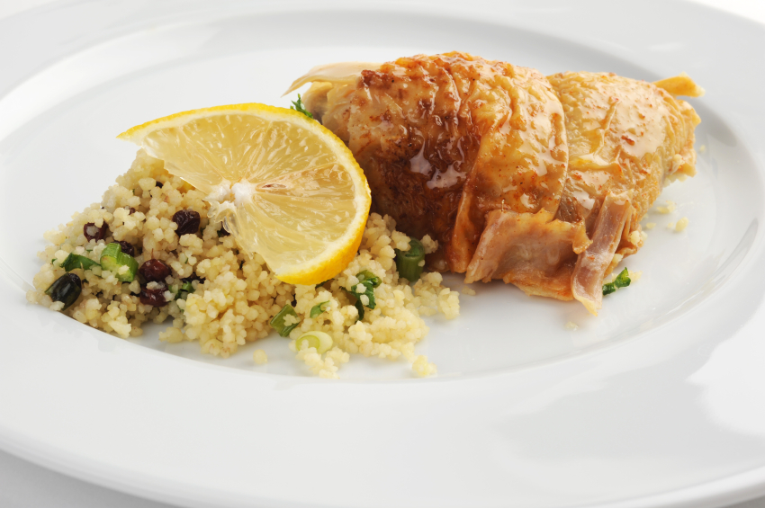 chicken on a plate with a lemon slice and grain