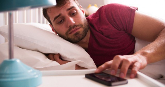 tired man being woken up by alarm on his phone
