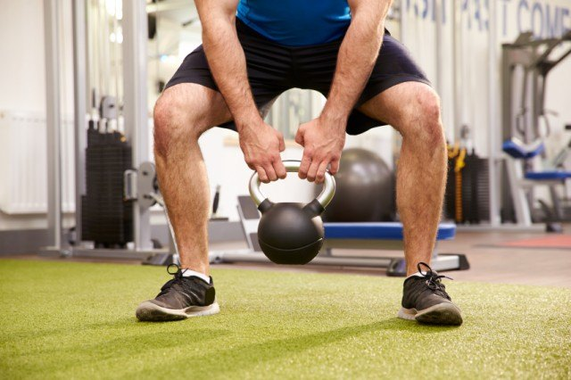 Man doing a kettlebell weighted squat at a gym.