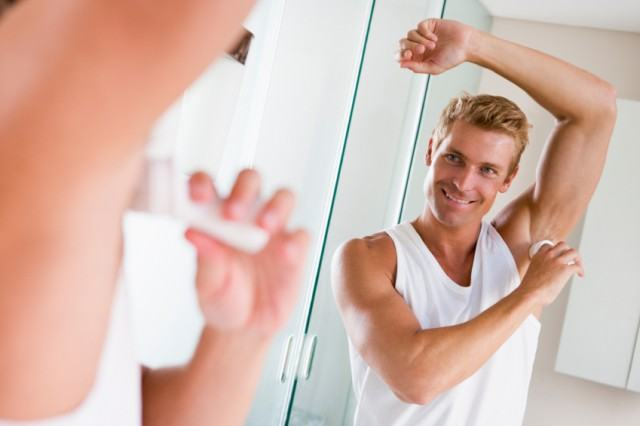 A man applies deodorant in front of his mirror.