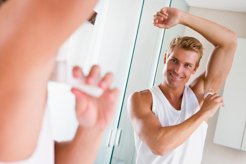 Man in bathroom applying deodorant