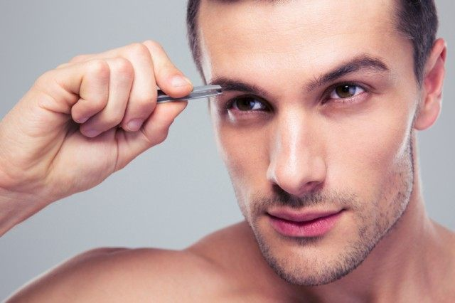 Man removing eyebrow hairs with tweezing, grooming