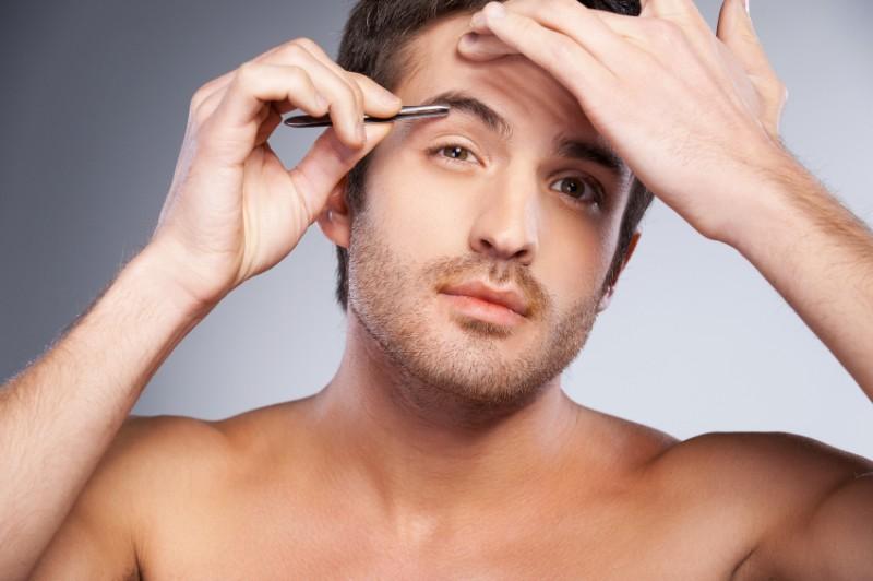Man tweezing his eyebrows