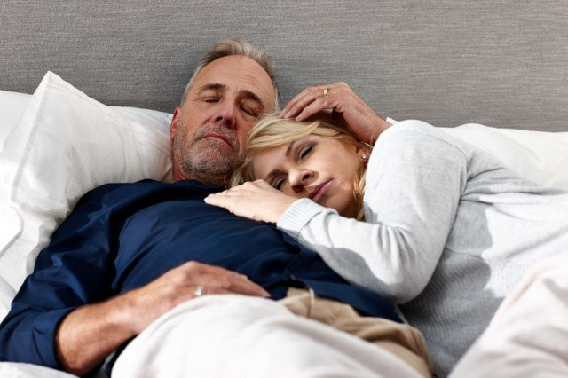 Man and woman sleeping together in bed.